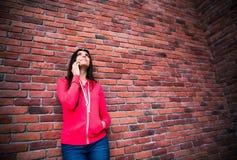 Lächelnde Frau, die am Telefon spricht und oben schaut Lizenzfreies Stockbild