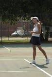 Lächelnde Frau, die Tennis spielt lizenzfreie stockbilder