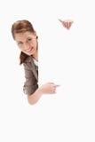 Lächelnde Frau, die um unbelegtes Zeichen zeigt Stockbild
