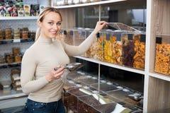 Lächelnde Frau, die verschiedene kandierte Früchte vorwählt Lizenzfreie Stockbilder