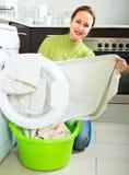 Lächelnde Frau, die Wäscherei tut Stockfoto