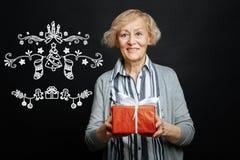 Lächelnde Frau, die Weihnachten und das Halten eines hellen Geschenkes feiert Stockbilder