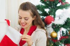 Lächelnde Frau, die Weihnachtssocken untersucht Stockfotografie