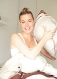 Lächelnde Frau, die Ziel mit einem Kissen nimmt Stockbild