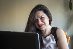 Lächelnde Frau, die zu Hause an ihrem Büro des Laptops arbeitet Lizenzfreie Stockfotos