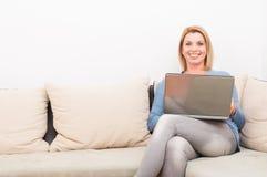 Lächelnde Frau, die zu Hause Laptop auf der Couch verwendet Lizenzfreie Stockfotografie