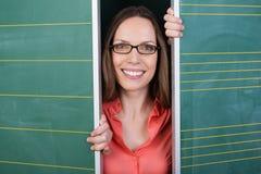 Lächelnde Frau, die zwischen zwei Tafeln blickt Stockfoto