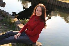 Lächelnde Frau durch See Stockbilder