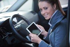 Lächelnde Frau in einem Auto mit Tablette Stockbild
