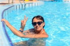 Lächelnde Frau in einem Swimmingpool stockfotografie