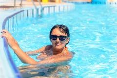 Lächelnde Frau in einem Swimmingpool lizenzfreie stockfotos