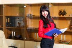 Lächelnde Frau in einer roten Bluse mit einem Ordner von Dokumenten Stockfotografie
