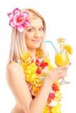 Lächelnde Frau gekleidet in einem trinkenden Cocktail des traditionellen Kostüms Stockfotos