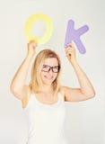 Lächelnde Frau hält das Wort okay Lizenzfreie Stockbilder