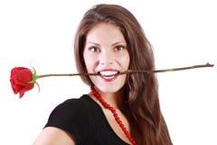 Lächelnde Frau hält Rotrose zwischen ihren Zähnen Lizenzfreie Stockfotografie
