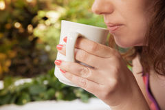 Lächelnde Frau hält weißen Tasse Kaffee in ihren Händen Stockfoto