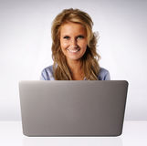 Lächelnde Frau hinter Laptop-Computer Stockbilder