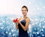 Lächelnde Frau im Abendkleid mit Geschenkbox Stockfotos