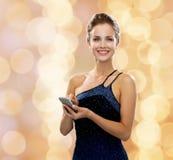 Lächelnde Frau im Abendkleid mit Smartphone Lizenzfreies Stockfoto