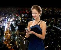 Lächelnde Frau im Abendkleid mit Smartphone Stockbilder
