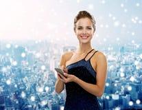 Lächelnde Frau im Abendkleid mit Smartphone Stockfoto
