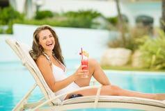 Lächelnde Frau im Badeanzug, der mit Cocktail sich entspannt lizenzfreies stockbild