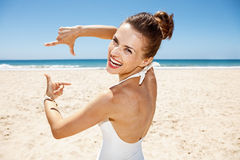 Lächelnde Frau im Badeanzug am sandigen Strand, der mit den Händen gestaltet Lizenzfreies Stockfoto