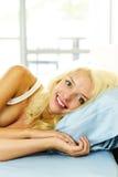 Lächelnde Frau im Bett morgens Stockfoto