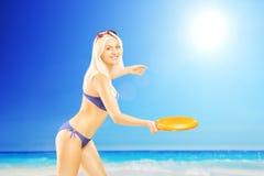 Lächelnde Frau im Bikini, der mit Frisbee auf einem Strand spielt Lizenzfreies Stockfoto