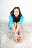 Lächelnde Frau im blauen Kleid sitzt auf weichem Teppich Stockfotografie