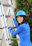 Lächelnde Frau im Blauhelm, der auf Aluminiumleiter klettert Lizenzfreie Stockfotos