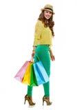 Lächelnde Frau im Hut mit den Einkaufstaschen, die zurück schauen Lizenzfreie Stockfotos