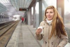 Lächelnde Frau im Mantel mit Kaffee an der Station Stockfoto
