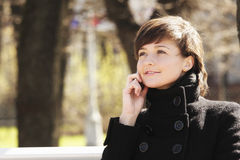 Lächelnde Frau im Park mit Mobiltelefon Stockfotografie