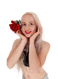 Lächelnde Frau im Porträt mit Rotrose Lizenzfreie Stockfotografie