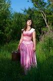 Lächelnde Frau im rosafarbenen Kleid mit Koffer Stockfotos