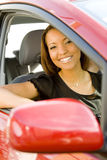 Lächelnde Frau im roten Auto stockbild
