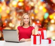 Lächelnde Frau im roten Hemd mit Geschenken und Laptop Stockbild