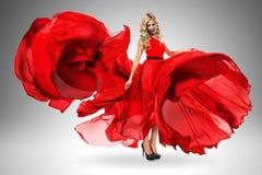 Lächelnde Frau im roten Kleid des großen Fliegens Stockbild