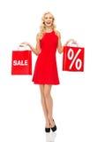 Lächelnde Frau im roten Kleid mit Einkaufstaschen Lizenzfreies Stockfoto