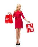 Lächelnde Frau im roten Kleid mit Einkaufstaschen Stockfoto