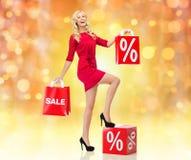Lächelnde Frau im roten Kleid mit Einkaufstaschen Lizenzfreie Stockbilder