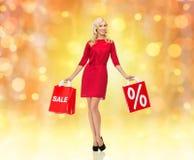 Lächelnde Frau im roten Kleid mit Einkaufstaschen Lizenzfreie Stockfotos