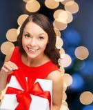 Lächelnde Frau im roten Kleid mit Geschenkbox lizenzfreie stockfotografie