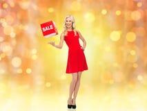 Lächelnde Frau im roten Kleid mit Verkauf unterzeichnen Stockbilder