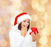 Lächelnde Frau im Sankt-Helferhut mit Geschenkbox Lizenzfreie Stockfotografie