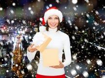 Lächelnde Frau im Sankt-Helferhut mit Geschenkbox Stockbilder