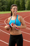 Lächelnde Frau im Sport-Büstenhalter mit laufenden Schuhen um ihren Stutzen Lizenzfreies Stockfoto
