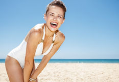 Lächelnde Frau im weißen Badeanzug am sandigen Strand an einem sonnigen Tag Stockfotos
