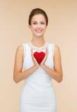 Lächelnde Frau im weißen Kleid mit rotem Herzen Lizenzfreie Stockfotografie